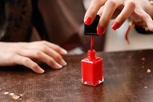 Red nail polish in application 3a0fa